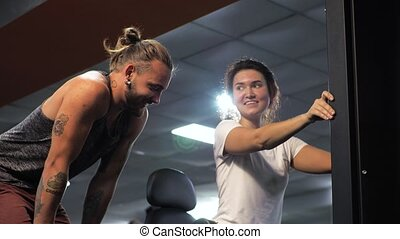 Gym. Lesson with a young funny trainer man. A beginner young woman shakes her legs on the simulator.