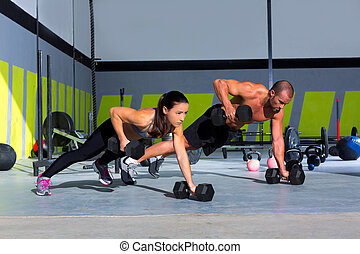 Gym man and woman push-up strength pushup with dumbbell in a...