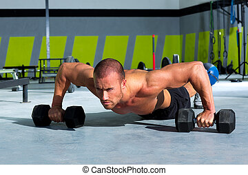 Gym man push-up strength pushup exercise with dumbbell in a...