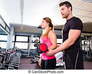 Gym personal trainer man with dumbbell woman