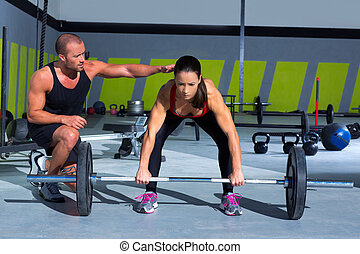 gym personal trainer man with weight lifting bar woman...