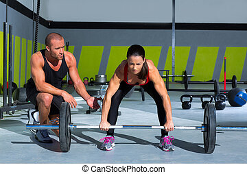 gym personal trainer man with weight lifting bar woman