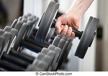 gym - close up of man holding weight in gym