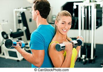 Gym training with dumbbells - couple in the gym, rivaling ...