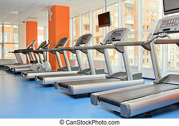 Gym with windows and running machines in fitness center