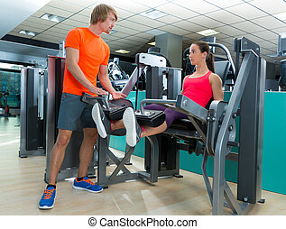 Gym woman leg extension with personal trainer