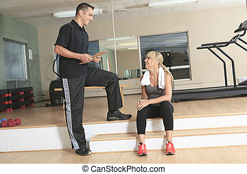 gym woman personal trainer man with weight training equipment