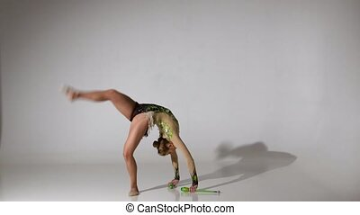 Gymnast doing back flips and standing on one leg. White...