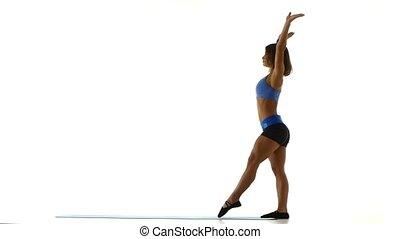 Gymnast doing cartwheel in a sport hall. White