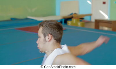 Gymnast doing double cork 360 degrees. Slow motion. Acrobat man practicing his skills at the gym