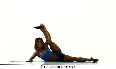 Gymnast doing stretching exercises. White