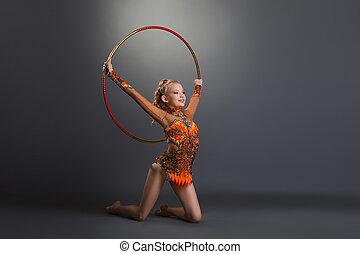 Gymnast girl performing with hoop at studio