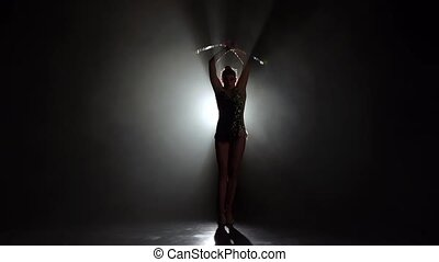 Gymnast in a nice suit with a mace. Black background. Slow motion. Silhouette