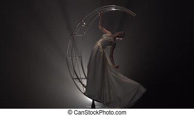 Gymnast in dress rotates on a metal construction in the form of a month. Smoke background