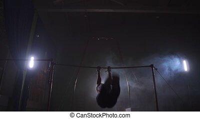 Gymnast on a dark background on the crossbar performs spins...