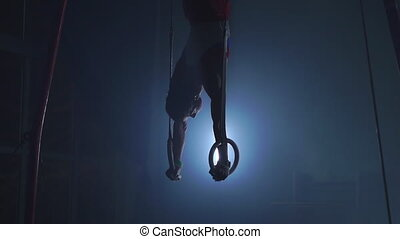 Gymnast on a dark background stands on his hands using rings...