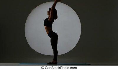 Gymnast performs a forward and backward tilt. Back light. Silhouette
