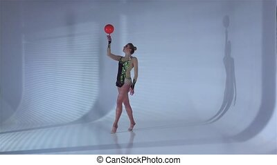 Gymnast professional spinning a ball on one finger. White background. Slow motion