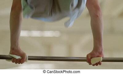 Gymnast spins on horizontal bar in the gym