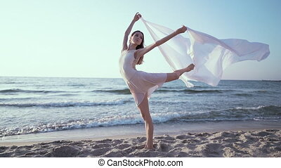 Gymnast stands in a difficult pose on the seashore and holds in hands long fabric, like sails fluttering in the wind. Concept of dance, tenderness, ballet.