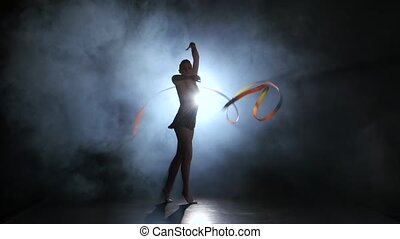 Gymnast with a ribbon in the hands circling in the smoke. Black background. Light rear. Silhouette