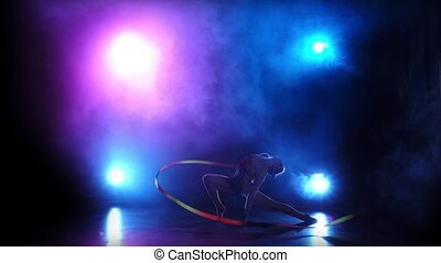 Gymnast with ribbon in his hands in the colored smoke. Silhouette. Black background. Slow motion. Light rear