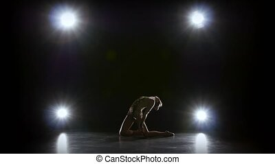 Gymnast with the ball in his hands doing acrobatic moves. Black background. Light rear