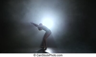 Gymnast with the ball in his hands doing acrobatic moves. Black background. Light rear. Silhouette