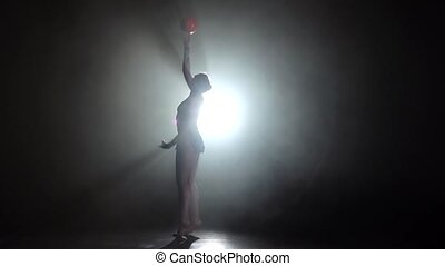Gymnast with the ball in his hands doing acrobatic moves. Black background. Light rear. Silhouette. Slow motion