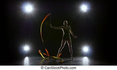 Gymnast with the ribbon in his hands doing acrobatic moves. Black background. Light rear