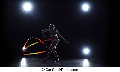 Gymnast with the ribbon in his hands doing acrobatic moves. Black background. Light rear. Slow motion