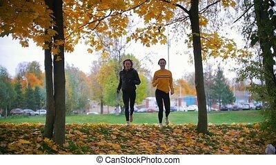 Gymnastic girls running towards the camera. Autumn park,...