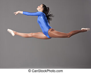 female gymnast doing splits in the air over grey background