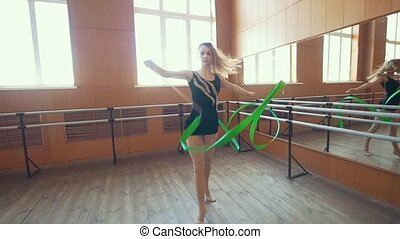 Gymnastic - young woman dancing with a green ribbon -training a gymnastics exercise, slow motion