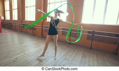 Gymnastic - young woman dancing with a green ribbon -training a gymnastics exercise, slow-motion