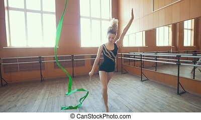 Gymnastic - young woman dancing with a green ribbon...