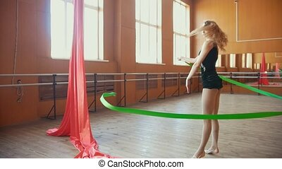 Gymnastic - young woman training a gymnastics exercise with a green ribbon, slow motion