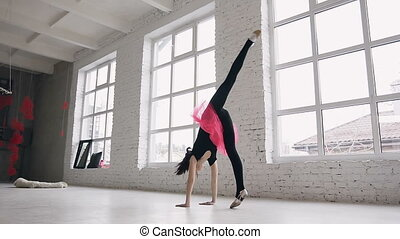 Gymnastics school. Cute gymnast girl performs a back flips with hands in the spacious white ballroom on windows background. Flexible girl doing five acrobatic back flips. Girl dressed in black bodysuit and pink skirt