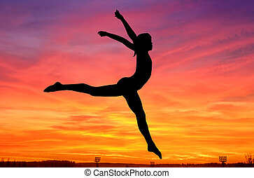 Gymnastics sky - Silhouette of a gymnast girl jumping at...