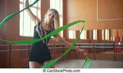 Gymnastics training - young woman have a gymnastics exercise with a green ribbon, slow-motion
