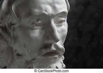 Gypsum copy of ancient statue John the Baptist head on dark textured background. Plaster sculpture man face.