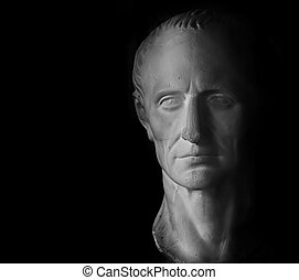 Gypsum model of head of Caesar on black background.