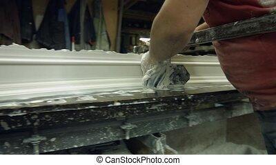 Gypsum shaping in workshop. Manufacturing of cornice by...