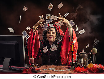 Mature Gypsy fortune teller is tossing up playing cards to predict future her online customer. Black-haired woman wears red-black blouse sitting at the desk with smoking candles and other occult items. Horizontal indoors shot on dark grange background