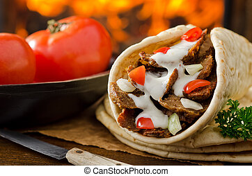 Gyro Donair - A gyro donair with onion and tomato against a ...