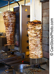 Gyro meat on rotating spit - Grilled meat used for making a...