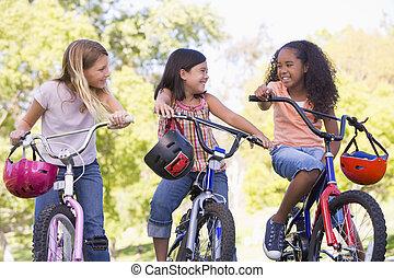 három, fiatal, bicycles, szabadban, lány friends, mosolygós