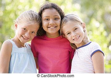három, fiatal lány, barátok, álló, szabadban, mosolygós