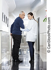 hátsó kilátás, közül, doktornő, gyalogló, noha, idősebb ember, türelmes