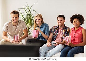 hållande ögonen på tv, popcorn, hem, vänner, lycklig